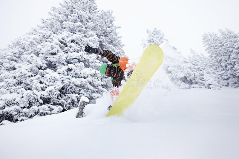 Lo Snowboarder che salta sul pendio dello sci immagine stock libera da diritti