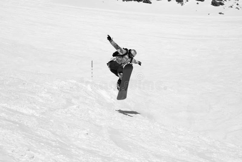 Lo Snowboarder che salta sul pendio nevoso dello sci fotografie stock