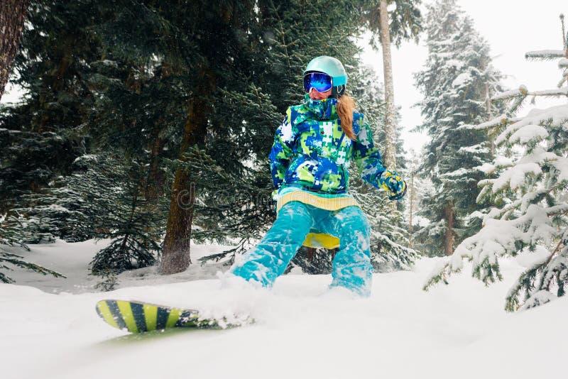 Lo Snowboarder con attrezzatura speciale è guidante e saltante molto velocemente nella foresta della montagna fotografie stock