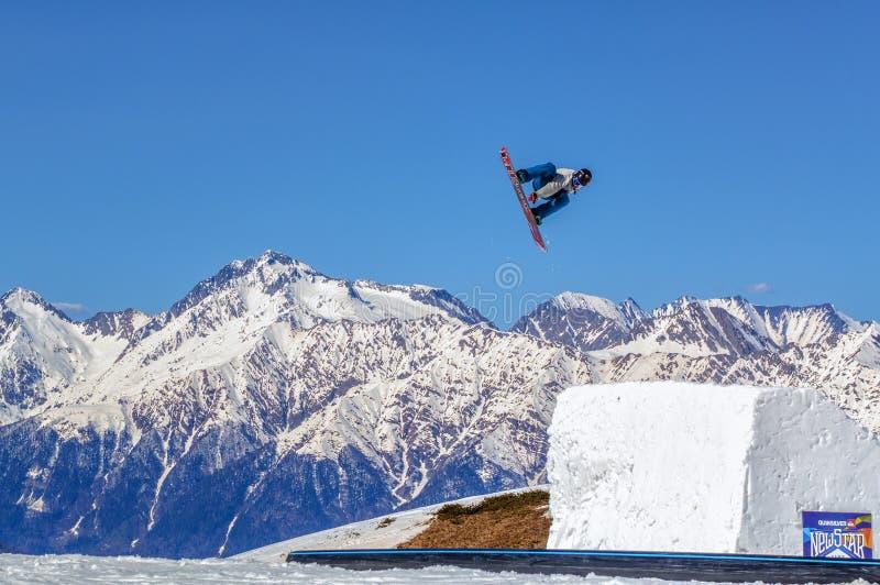 Lo snowboarder dell'uomo pilota lo stile libero da un salto sul picco di montagna di Chugush e sul fondo del cielo blu Soci, Cauc immagine stock libera da diritti
