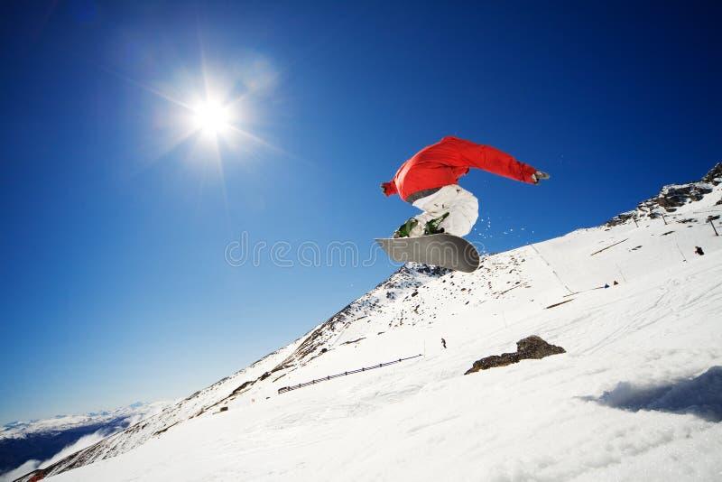 Lo Snowboarder salta immagine stock