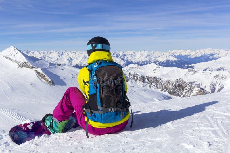 Lo Snowboarder si siede su un pendio con la sua parte posteriore e sugli sguardi al panorama delle montagne immagine stock libera da diritti