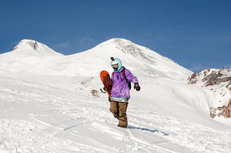 Lo Snowboarder sta e cammina sui pendii di montagna di un vulcano estinto Elbrus immagine stock
