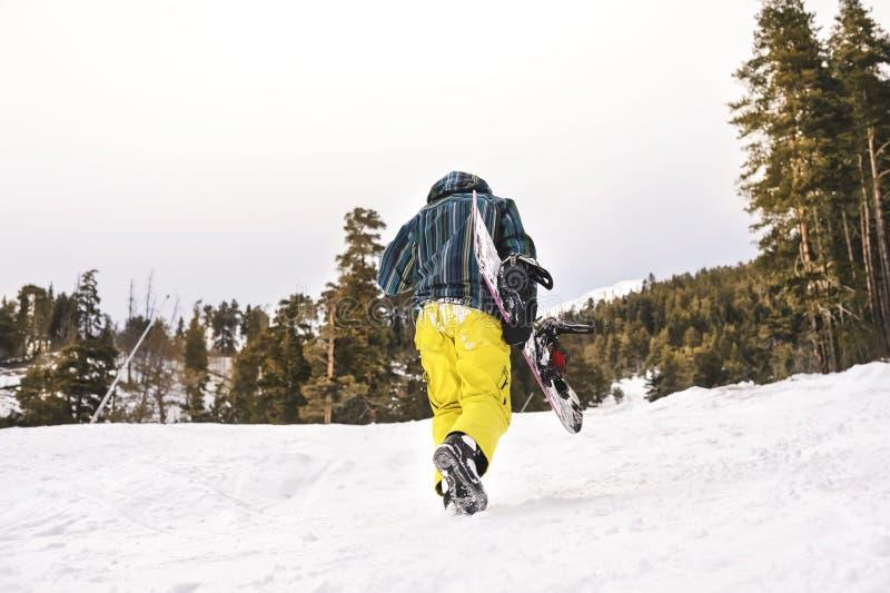 Lo snowboarder stanco va sul pendio dello sci immagini stock