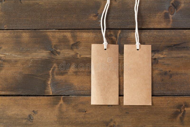 Lo spazio in bianco identifica le etichette con corda su una tavola di legno rustica immagini stock
