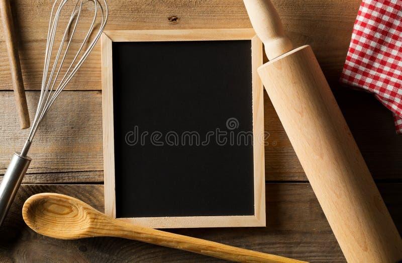 Lo spazio in bianco, lavagna vuota e nera con il matterello di legno, cavo sbatte ed asciugamano di piatto a quadretti rosso post fotografia stock libera da diritti