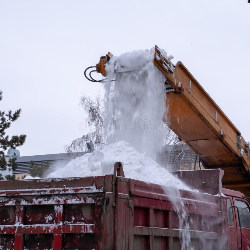 Lo spazzaneve pulisce la città dopo una tempesta della neve Primo piano Trattore dell'aratro di neve e lavoro del camion sulla vi fotografia stock