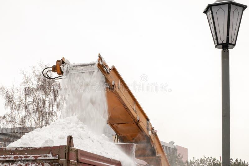 Lo spazzaneve pulisce la città dopo una tempesta della neve Primo piano trattore di Neve-rimozione e lavoro del camion vicino all fotografia stock libera da diritti