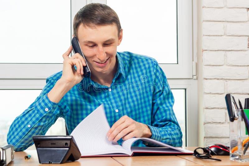 Lo specialista allegro nell'ufficio sta parlando sul telefono e sta sfogliando i documenti fotografia stock libera da diritti