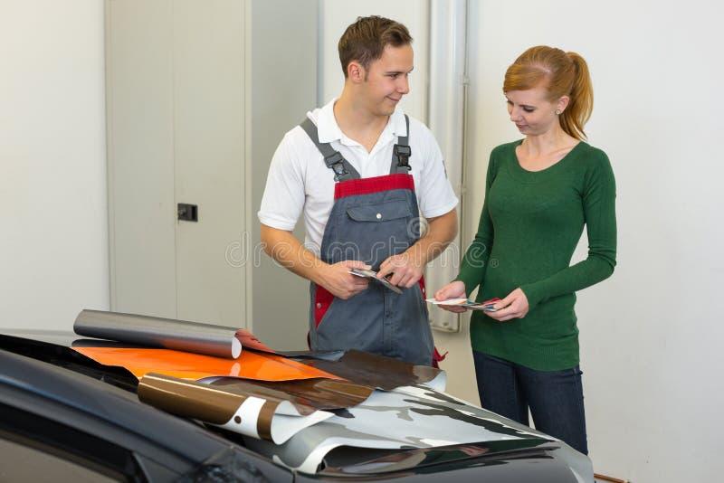 Lo specialista marcante a caldo dell'automobile consulta un cliente circa le stagnole adesive o i film per lo spostamento automati fotografie stock