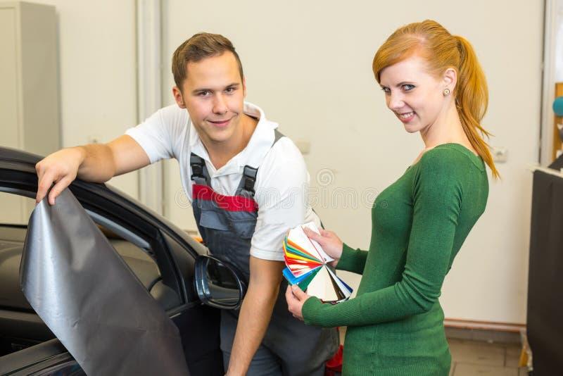 Lo specialista marcante a caldo dell'automobile consulta un cliente circa le stagnole adesive o i film per lo spostamento automati fotografie stock libere da diritti