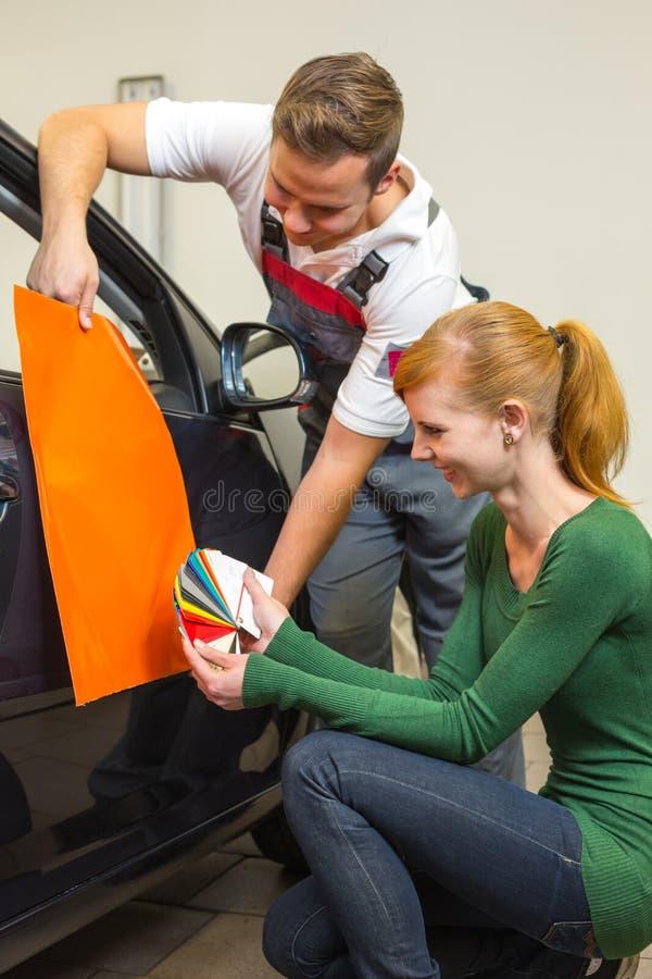 Lo specialista marcante a caldo dell'automobile consulta un cliente circa le stagnole adesive o i film per lo spostamento automati fotografia stock
