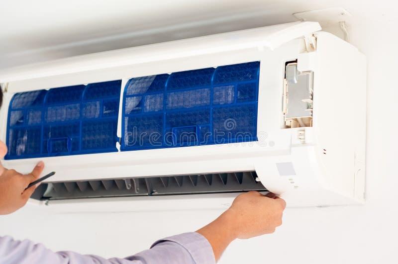 Lo specialista pulisce e ripara il condizionatore d'aria della parete fotografia stock libera da diritti