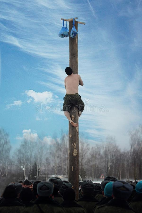 Lo spettacolo militare a tempo il tempo libero dai militari di servizio scala su una colonna di legno liscia fotografia stock libera da diritti