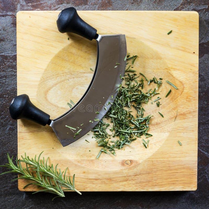Lo spezzettamento dei rosmarini a pezzi freschi con Mezzaluna ha curvato il coltello a bordo della vista superiore fotografia stock libera da diritti