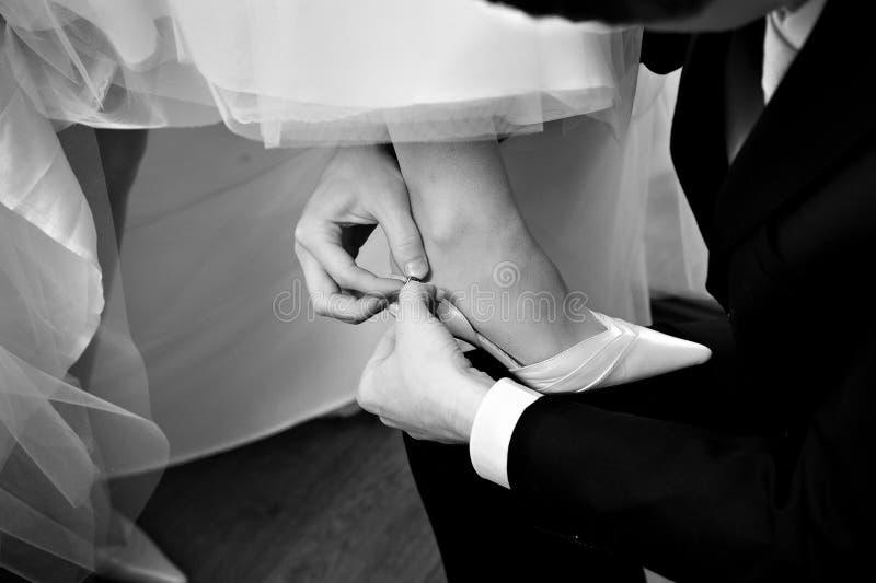 Lo sposo abbottona la sposa dei pattini fotografia stock
