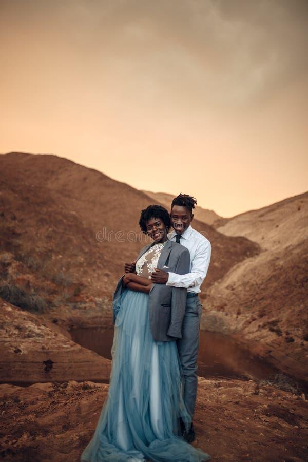 Lo sposo abbraccia la sua sposa vestita in suo rivestimento in canyon al tramonto fotografia stock libera da diritti