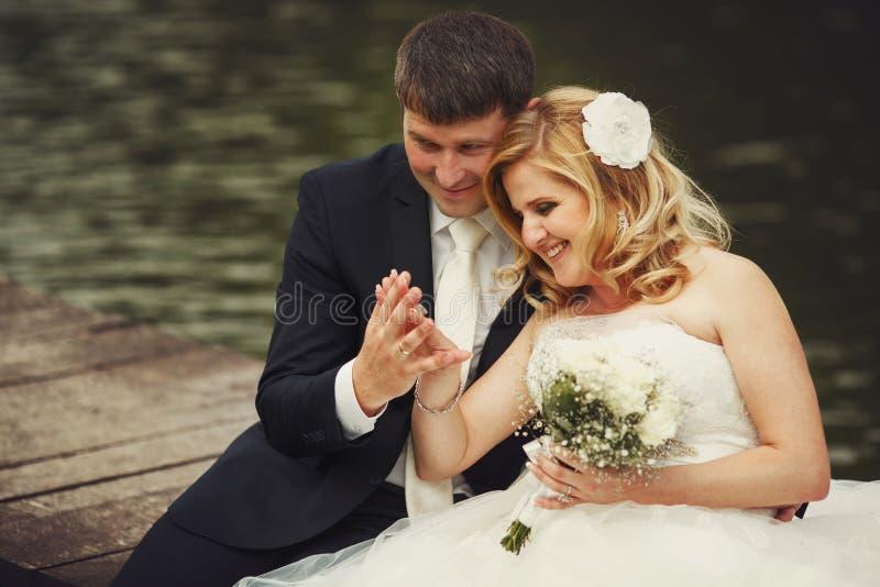 Lo sposo ammira il braccio della sposa con una fede nuziale mentre si siede sulla t fotografia stock libera da diritti