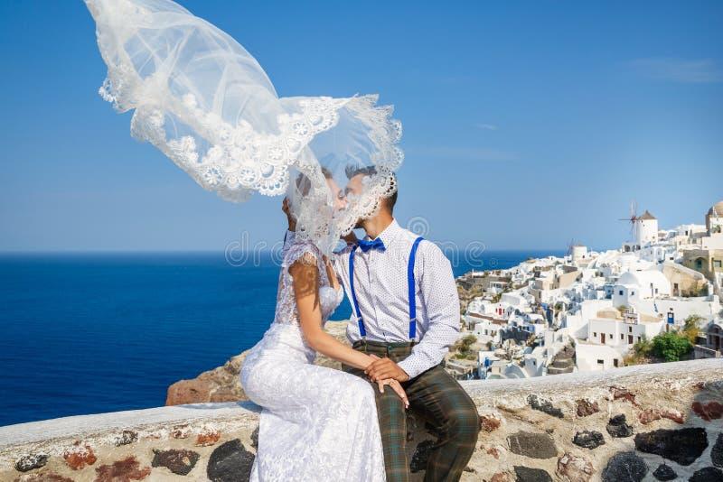 Lo sposo bacia la sposa, sbattimenti di velo nel vento fotografia stock libera da diritti