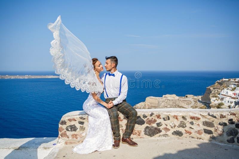 Lo sposo bacia la sposa, sbattimenti di velo nel vento fotografia stock