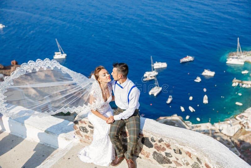 Lo sposo bacia la sposa, sbattimenti di velo nel vento immagini stock libere da diritti