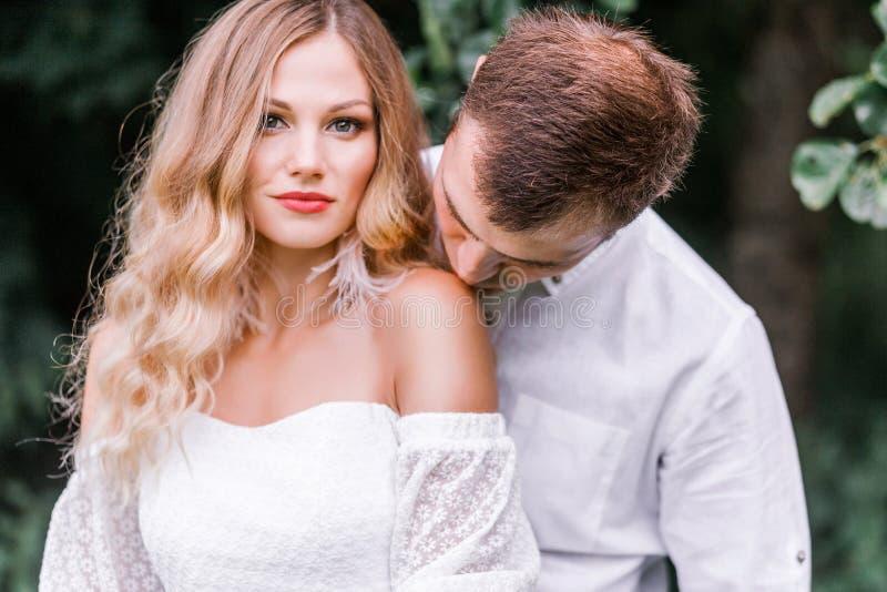 Lo sposo bacia la sposa sulla spalla nuda fotografie stock libere da diritti