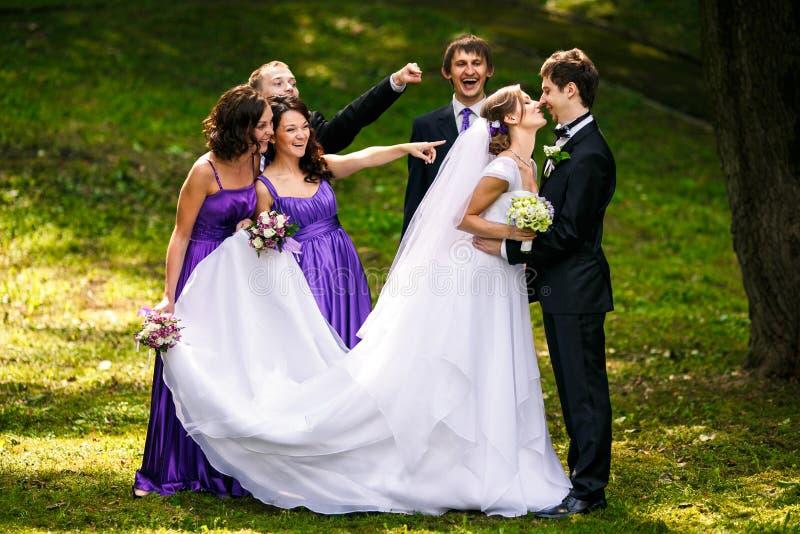 Lo sposo bacia una sposa mentre i suoi amici fa smorfie dietro lui fotografie stock
