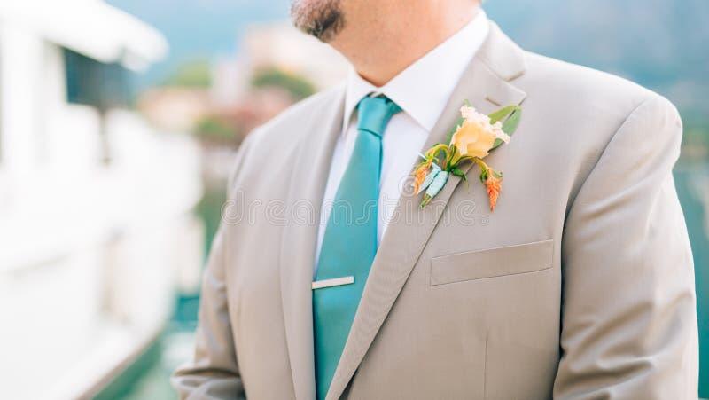 Lo sposo con un boutonniere della barba sul risvolto di un jacke leggero immagine stock libera da diritti