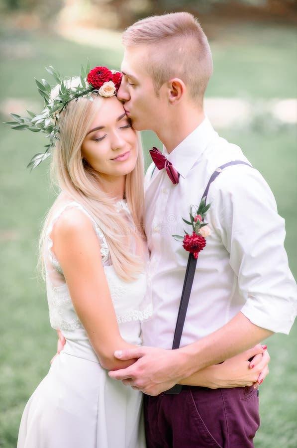Lo sposo dei giovani bacia la fronte del ` s della sposa mentre abbraccia l'offerta il suo wa fotografia stock