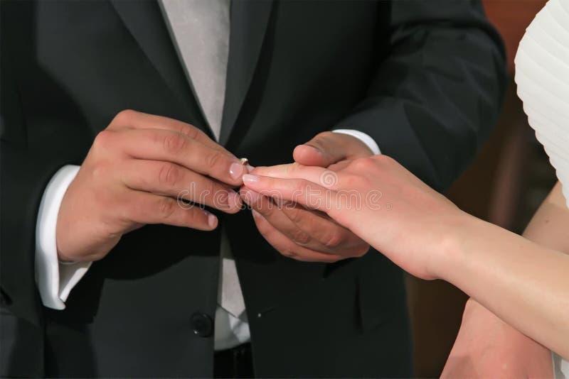 Lo sposo di Uthe mette sopra un anello di fidanzamento sul dito della sposa immagine stock libera da diritti