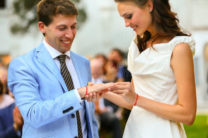 Lo sposo e la sposa alla moda ricchi hanno messo l'anello vicino all'arco di sunflowe fotografia stock libera da diritti