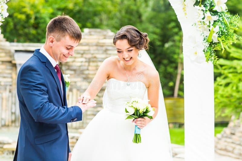 Lo sposo e la sposa sta indossando un anello sul dito, cerimonia di nozze Oro, simbolo, religione, amore immagini stock