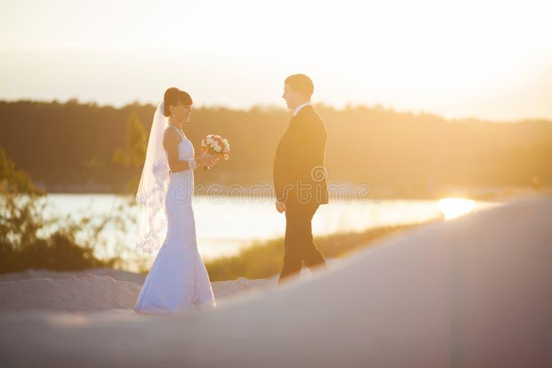 Lo sposo e la sposa sta posando sul bello tramonto del fondo sopra immagini stock libere da diritti