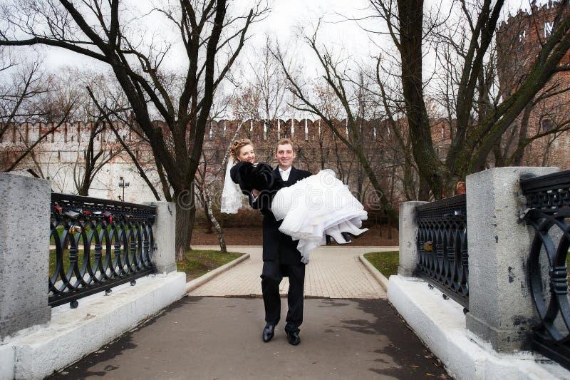 Lo sposo felice trasporta la sua sposa in sue braccia fotografia stock
