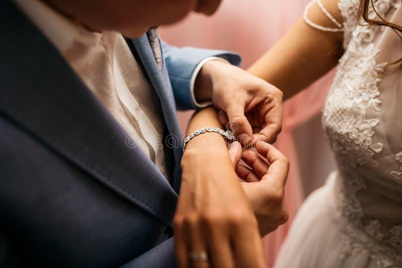 Lo sposo fissa il braccialetto sul polso del ` s della sposa fotografia stock libera da diritti