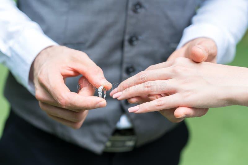 Lo sposo indossa l'anello del ` s della sposa immagini stock