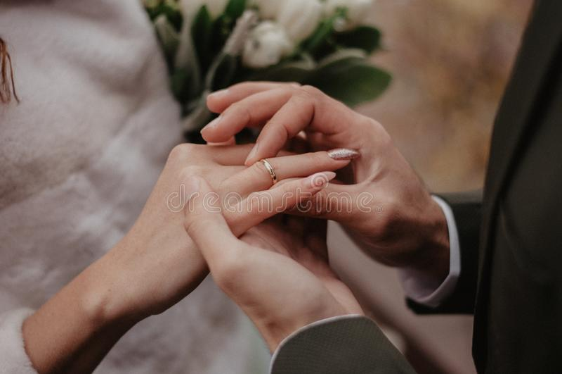 Lo sposo indossa la fede nuziale dorata sul dito della sposa fotografie stock