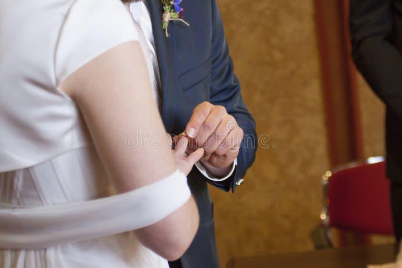 Lo sposo mette l'anello del ` s della sposa sul suo dito fotografie stock