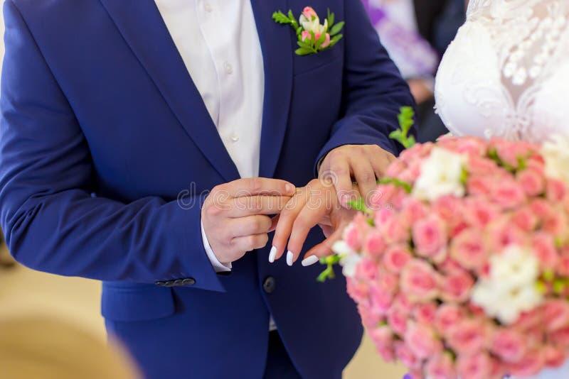 Lo sposo mette l'anello della sposa fotografia stock