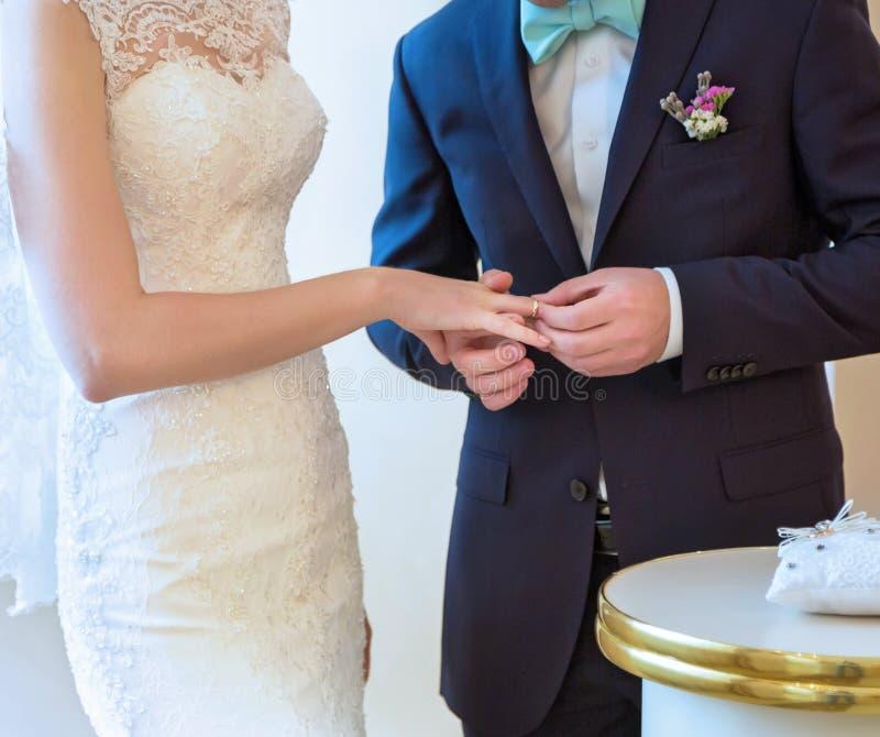 Lo sposo mette l'anello della sposa fotografia stock libera da diritti