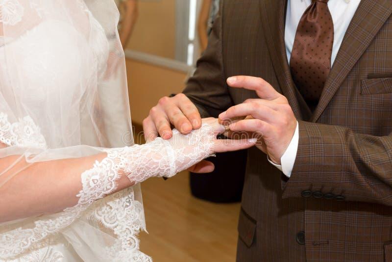 Lo sposo mette l'anello sul dito nuziale fotografie stock libere da diritti