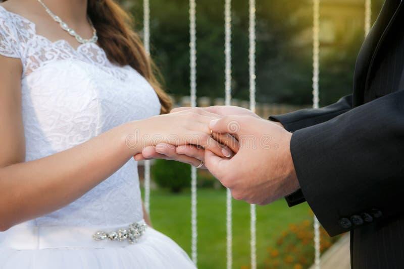 Lo sposo mette la fede nuziale sul dito della sposa fotografia stock libera da diritti