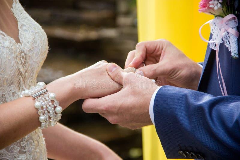Lo sposo mette sopra l'anello del ` s della sposa immagini stock libere da diritti