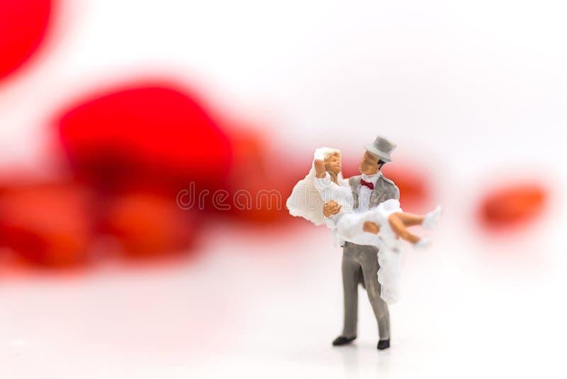Lo sposo porta la sposa in un vestito da sposa bianco su un giorno delle nozze, con un cuore rosso come terra posteriore fotografie stock