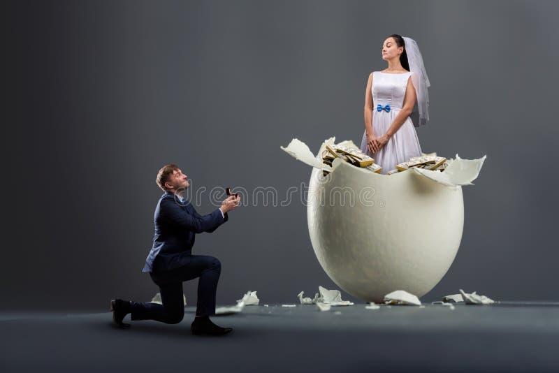 Lo sposo presenta la proposta, sposa nelle coperture fotografia stock