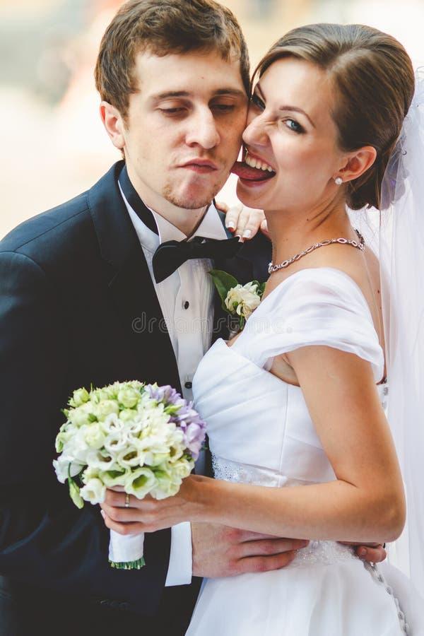 Lo sposo racconta le storie della sposa che cammina lungo le ferrovie sullo stre immagini stock
