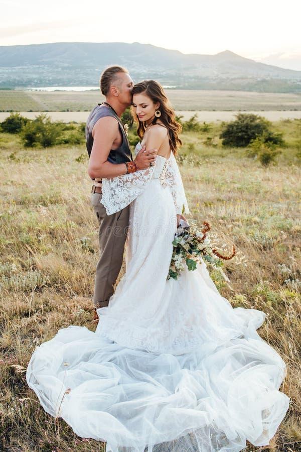 Lo sposo si è vestito nello stile del boho delicatamente bacia la sposa immagine stock libera da diritti