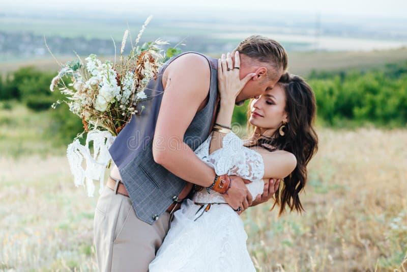 Lo sposo si è vestito nello stile del boho delicatamente bacia la sposa fotografia stock