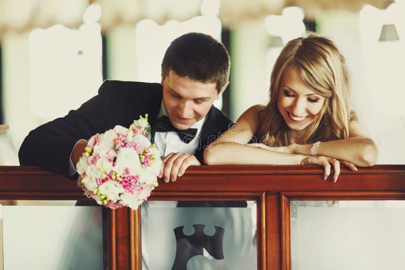Lo sposo si diverte mentre siitting con una sposa al piano immagini stock