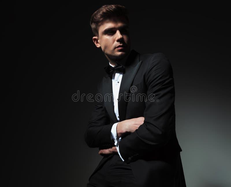 Lo sposo sicuro con le mani ha piegato gli sguardi per parteggiare fotografia stock libera da diritti